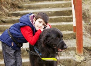 Noah Coughlan with Picasso, his autism assistance dog